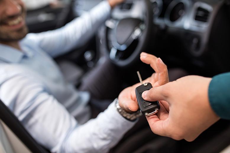 Female hand handing a man in a car a key - Georgian International