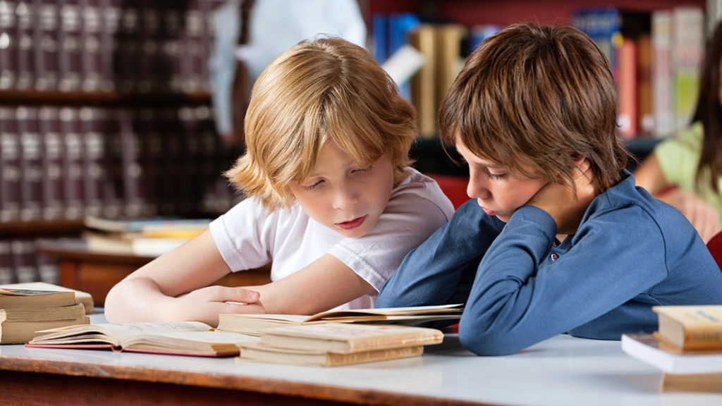 Two Young boys reading books at a table in a library