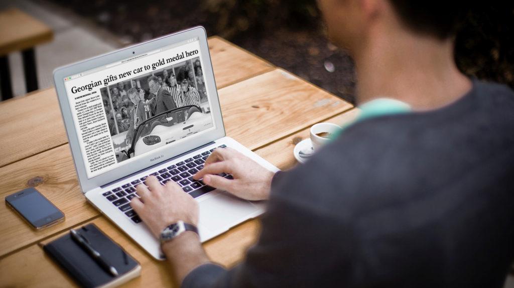 Person on laptop looking at Georgian International Gold Medal Hero Story