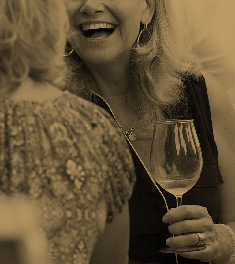 Woman holding a wine glass and laughing