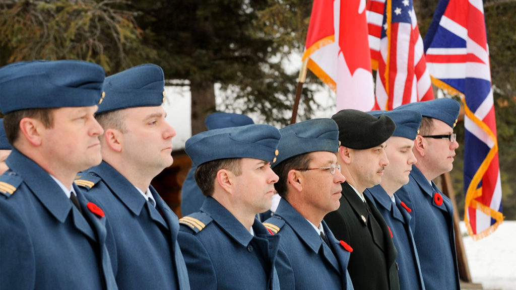 Veterans Standing in front Canadian, American, and British Flags
